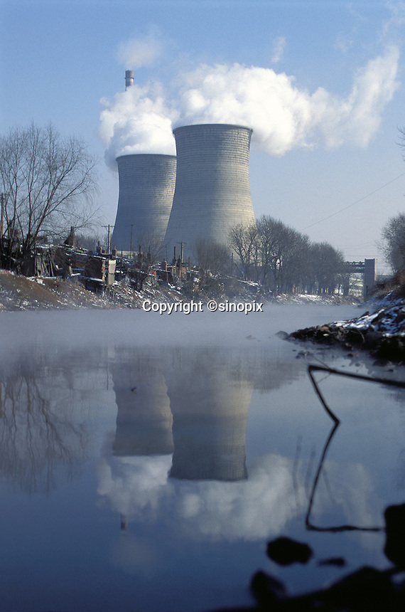 A coal fired power station in Shenyang, China, emits smoke through huge chimneys while pollluting the nearby river with industrial wastes.