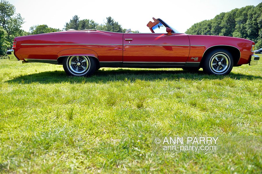 Old Westbury, New York, United States. 7th June 2015. A red 1975 Pontiac Grand Ville convertible, seen from right side, is shown at the 50th Annual Spring Meet Car Show sponsored by Greater New York Region Antique Automobile Club of America. Over 1,000 antique, classic, and custom cars participated at the popular Long Island vintage car show held at historic Old Westbury Gardens.