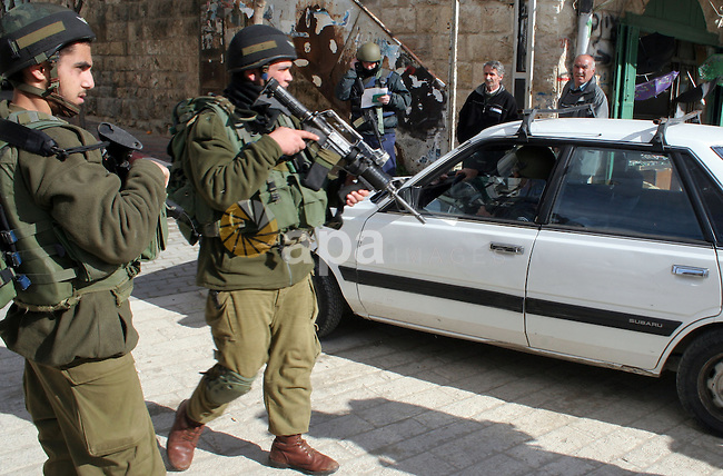 Israeli soldiers stand guard as an Israeli policeman search a Palestinian car near an Israeli checkpoint in the old city of West Bank city of Hebron, January 21, 2010. Photo by Najeh Hashlamoun