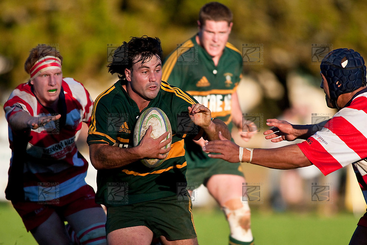 Armyn Sanders looks to avoid the tackle of Siasi Tuatao. Counties Manukau Premier Club Rugby game between Pukekohe & Karaka played at Colin Lawrie Fields Pukekohe on Saturday May22nd 2010..Pukekohe won the game 32 -28 after trailling 3 - 22 at halftime.