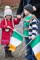 St Patricks Day parade High Street Digbeth.Two young kids holding tricolours watching parade