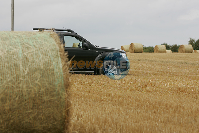 A farmers 4x4 parked in the field as round bails of Hay are loaded onto a trailer in the field after the harvest in August 2006.Photo: Fran Caffrey/ Newsfile.
