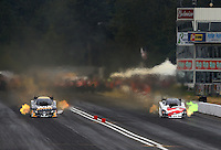 Aug. 3, 2013; Kent, WA, USA: NHRA funny car driver Tony Pedregon (left) races alongside brother Cruz Pedregon during qualifying for the Northwest Nationals at Pacific Raceways. Mandatory Credit: Mark J. Rebilas-USA TODAY Sports
