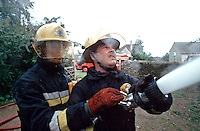 Firefighters fighting a house fire. They are aiming the main jet through one of the first floor windows. This image may only be used to portray the subject in a positive manner..©shoutpictures.com..john@shoutpictures.com