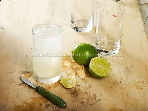 Moscow mule cocktail with limes, paring knife, on a wooden cutting board