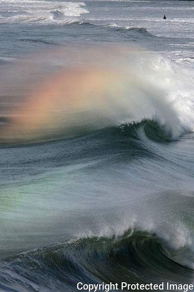 o.weather.1.121806.ww.jpg/bill wechter/Rainbow colors are reflected from spray blown off the crest of waves by an offshore breeze Monday on the north side of the Oceanside Pier.