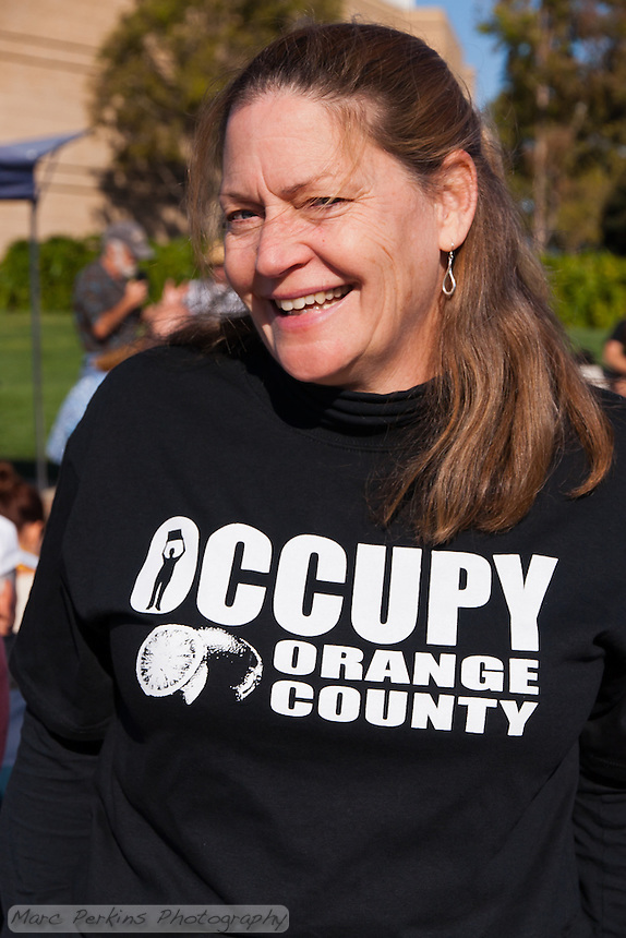 Marcella wears an Occupy Orange County shirt at the Occupy Orange County, Irvine camp on November 5.  One of the speakers talks behind her.