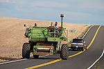 "Jeff Yerbich and his team heard ""Free Beer (Tomorrow)"" their vintage John Deere combine on the road from their farm in Kahlotus, Wash. to the combine destruction derby in Lind, Wash. about 25 miles away through the rolling wheat fields along Washington SR 21"