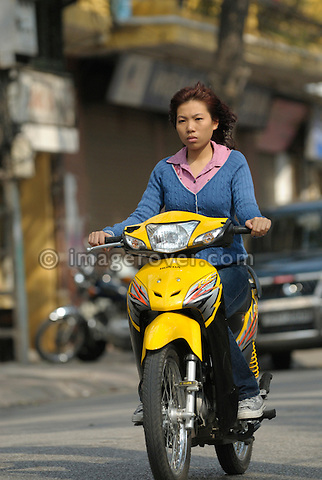 Asia, Vietnam, Hanoi. Hanoi old quarter. Young vietnamese woman rushing on her yellow motorbike through Hanoi.