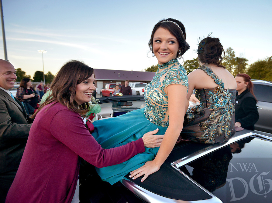 STAFF PHOTO BEN GOFF  @NWABenGoff -- 10/17/14 Jamie Dotson, left, helps her daughter Shelby Rae Dotson, 15, freshman homecoming maid, get situated in a convertible while preparing to ride into Huntsville's Eagle Stadium for pre-game festivities before the football game between Lincoln and Huntsville on Friday October 17, 2014.