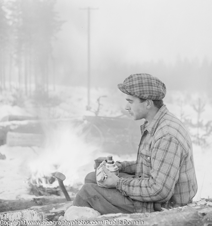 Forestry working in winter taking a meal break with thermos flask, Finland 1950s