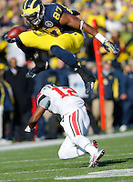 Michigan Wolverines tight end Devin Funchess (87) leaps over Ohio State Buckeyes cornerback Doran Grant (12) as he runs the ball in the second quarter of the college football game between the Ohio State Buckeyes and the Michigan Wolverines at Michigan Stadium in Ann Arbor, MI Saturday afternoon, November 30, 2013. The Ohio State Buckeyes defeated the Michigan Wolverines 42 - 41. (The Columbus Dispatch / Eamon Queeney)