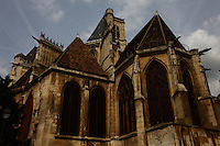 The top of the back of the Saint Gervais church (XVI-XVII century) in the Marais, Paris, with its high glass windows, its typical ancient roof and its gargoyles. There was a typical beautiful Parisian sky with sun and clouds. Digitally Improved Photo.