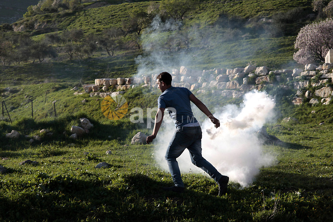 A Palestinian protester throws back a tear gas canister fired by Israeli security forces during clashes at Hawwara military checkpoint near the West Bank city of Nablus on February 26, 2013. Increased protests in the West Bank after the killing of a Palestinian Prisoner Arafat Jaradat, 30, whose death in an Israeli jail on 23 February sparked riots across the Israeli-occupied West Bank. Palestinians claim he died of torture. Israel says the initial autopsy could not determine the cause of death and further tests were needed. Photo by Nedal Eshtayah