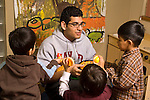 Preschool New York City ages 4-5 high school student volunteering in the classroom interaction with group of boys