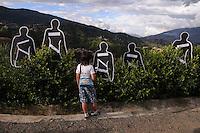 """MEDELLÍN - COLOMBIA, 07-06-2014. Una niña pasa frente a las siluetas con los nombres de las personas desaparecidas en """"La Escombrera"""", en la Comuna 13 de Medellín, durante una vigilia contra las desapariciones forzadas. En 2002, Medellín fue sacudido por la violencia después de la decisión del Gobierno de recuperar un sector de la ciudad disputada por los paramilitares de derecha y las milicias de izquierda. Según los familiares de las víctimas, en la operación ordenada el 16 de octubre de 2002 por el presidente Álvaro Uribe, decenas de personas murieron, más de 100 personas resultaron heridas, 98 personas desaparecieron y más de 200 familias fueron desplazadas./  A girl walks in front of the silouethes with the names of missing persons in """"La Escombrera"""" in Comuna 13 in Medellín, during a vigil against forced disappearances. In 2002, Medellín was rocked by violence following the government's decision to recover a part of the city disputed by right-wing paramilitaries and leftist militias. According to relatives of the victims, the orderly operation on October 16, 2002 by President Alvaro Uribe, dozens of people were killed, over 100 people were injured, 98 people missing and more than 200 families were displaced. Photo: VizzorImage/Luis Rios/STR"""