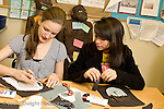 Education Middle School grade 8 art activity cut paper self portraits two female students at work horizontal