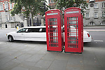 White stretch limo and two old style red telephone boxes in central London.