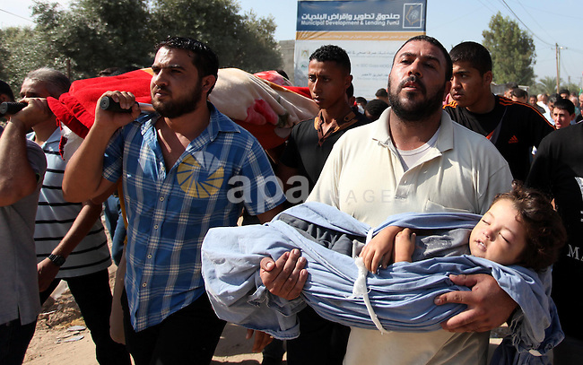 "Relatives carry the body of two-year-old Palestinian girl Rahaf, during the funeral of the toddler and her pregnant mother on October 11, 2015, at the al-Nusairat refugee camp, in central Gaza Strip. A pregnant Palestinian mother and her toddler daughter were killed in the air strike in the Zeitun sector south of Gaza City while three others were still trapped under the ruins of a house, medical sources said. Israel said it had targeted ""two Hamas weapon manufacturing facilities"" in response to two rocket launches at Israel the day before. Photo by Ashraf Amra"