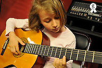 Girl (7-6) playing accoustic guitar in recording studio (Licence this image exclusively with Getty: http://www.gettyimages.com/detail/81867385 )