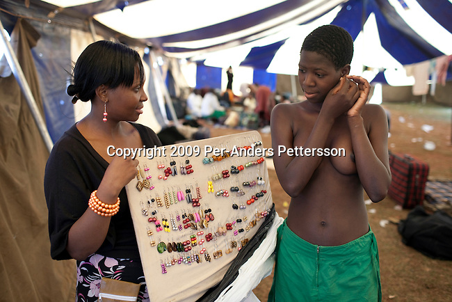 LUDZIDZINI, SWAZILAND - AUGUST 29: An unidentified girl buys earrings from a trader before a traditional Reed dance ceremony at the Royal Palace on August 29, 2009, in Ludzidzini, Swaziland. About 80.000 virgins from all over the country attended this yearly event, which goes on for a week and which is the biggest in Swazi culture. Many of the girls stayed in tents and slept on the ground. It was founded to celebrate the beauty of Swazi women and girls. King Mswati III, and absolute monarch, was born in 1968 and he has 14 wives and many children. The king danced with his men in front of the 80.000 girls. Many of the girls hope to get noticed by the king and to be chosen as a future wife, a ticket from poverty and into a life of privilege and luxury. The country is one of the poorest in the world and it is struggling with a high prevalence of HIV-Aids and severe poverty. (Photo by: Per-Anders Pettersson)....