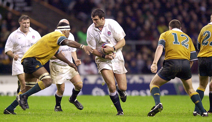 Photo. Richard Lane. .England vs Australia - Twickenham.18.11.00.Martin Johnson about to be tackled by Jim Williams.