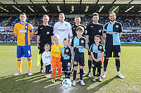 Team captains, mascots and officials line up ahead of the Sky Bet League 2 match between Wycombe Wanderers and Mansfield Town at Adams Park, High Wycombe, England on 25 March 2016. Photo by David Horn.