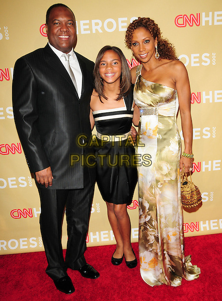 RODNEY PEETE, DAUGHTER RYAN & HOLLY ROBINSON PEETE .at The 3rd Annual CNN Heroes: An All-Star Tribute held at The Kodak Theatre in Hollywood, California, USA,  November 21st 2009                                                                   .full length family black suit dress shiny print gold one shoulder maxi long pattern floral bag family kid child mother father parents couple husband wife married .CAP/RKE/DVS.©DVS/RockinExposures/Capital Pictures