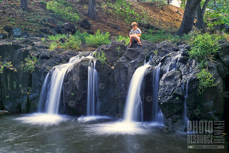 Peaceful waikahulu falls with young boy resting near the waterfalls