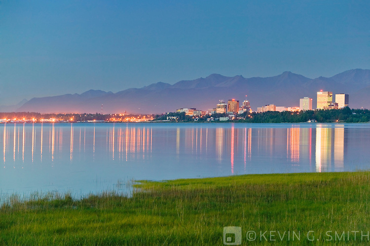 The Anchorage city skyline at twilight, buildings reflected in the water at high tide, summer, Anchorage Alaska