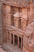 Treasury of the Pharaohs or Khazneh Firaoun, 100 BC - 200 AD, Petra, Ma'an, Jordan. Originally built as a royal tomb, the treasury is so called after a belief that pirates hid their treasure in an urn held here. Carved into the rock face opposite the end of the Siq, the 40m high treasury has a Hellenistic facade with three bare inner rooms. Petra was the capital and royal city of the Nabateans, Arabic desert nomads. Man standing at the bottom shows the scale of the edifice. Picture by Manuel Cohen
