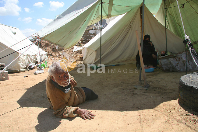 Homeless, handicapped Palestinian man Mohammed Daher, 60, sits outside his tent in eastern Jabalya refugee camp March 29, 2009 . His family's house and his wheelchair were destroyed during Israel's three-week long offensive in Gaza Strip last January.  APAIMAGES PHOTO / Ashraf Amra