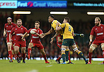 Australia full back Israel Folau gets the ball way as he's tackled by Liam Williams.<br /> Dove Men Series 2014<br /> Wales v Australia<br /> Millennium Stadium<br /> 08.11.14<br /> ©Steve Pope-SPORTINGWALES