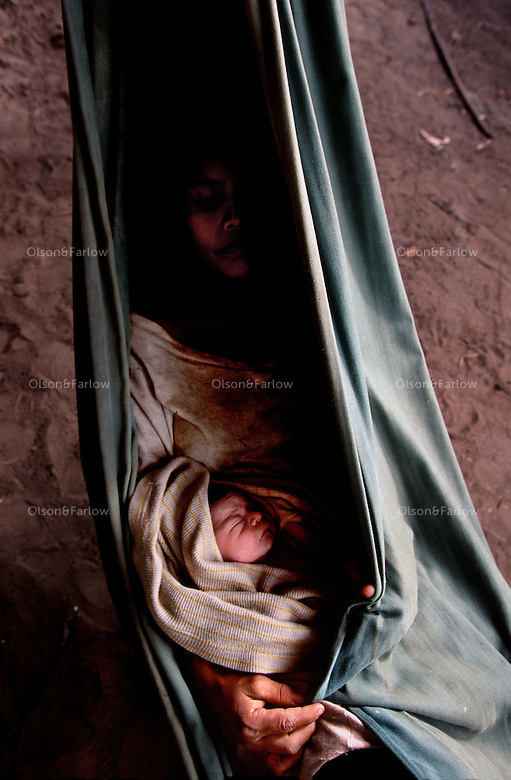 Outside town of Chenapow, Mother with newborn child suffers from malaria.
