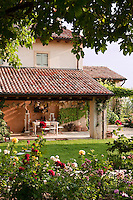 Looking across the rosebed and lawn to the porch with its terracotta tiled roof