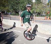 A middle-aged unicyclist rides across the Brooklyn Bridge during 13-mile trip to Coney Island on Friday, August 29, 2014 as part of the NYC Unicycle Festival. The convergence of unicyclists was the start of the 3-day Fifth Annual New York City Unicycle Festival which besides the ride, features performances, classes and just plain fun with events happening on Governor's Island. (© Richard B. Levine)