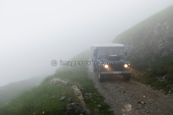 Land Rover Series 2a Ambulance based Defender 110 300tdi camper conversion crossing the unsurfaced Stol mountain pass from Sedlo to Zaga in the Julian Alps, Slovenia. --- No releases available, but releases may not be necessary for certain uses. Automotive trademarks are the property of the trademark holder, authorization may be needed for some uses.
