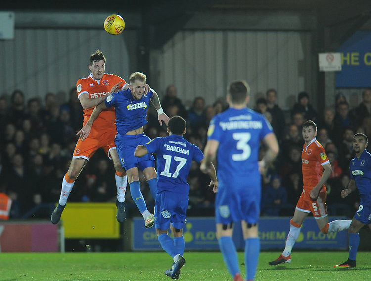 Blackpool's Ben Heneghan heads clear despite the attentions of AFC Wimbledon's Mitch Pinnock<br /> <br /> Photographer Kevin Barnes/CameraSport<br /> <br /> The EFL Sky Bet League One - AFC Wimbledon v Blackpool - Saturday 29th December 2018 - Kingsmeadow Stadium - London<br /> <br /> World Copyright © 2018 CameraSport. All rights reserved. 43 Linden Ave. Countesthorpe. Leicester. England. LE8 5PG - Tel: +44 (0) 116 277 4147 - admin@camerasport.com - www.camerasport.com
