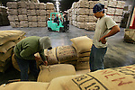 EDISON, NJ - MAY 11, 2006:  Alfredo Fero (L) and Tomas Fiero (R) move coffee inside an RPM warehouse on May 11, 2006 in Edison, NJ.  The NYBOT sanctioned warehouse can hold approximately 65 million pounds of coffee, roughly 450,000 bags.  According to the Green Coffee Association's March '06 report, RPM has about 50% of the green coffee market in the United States.  (Photo by Michael Nagle)