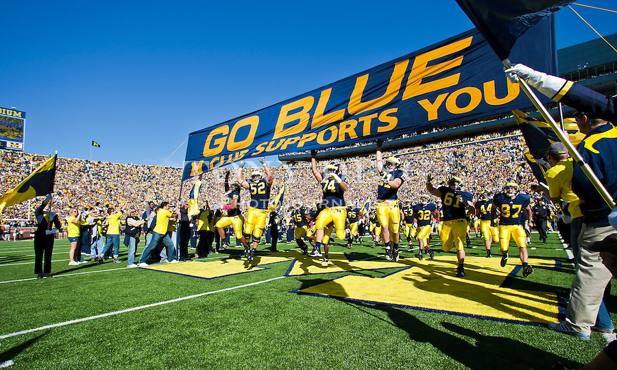 "Michigan players take the field by running under the traditional ""GO BLUE"" banner before an NCAA college football game with Iowa, Saturday, Oct. 16, 2010, in Ann Arbor, Mich. (AP Photo/Tony Ding)"