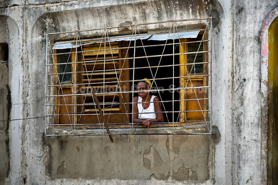"""A Cuban woman looks from the barred window in the apartment block in Abel Santamaría, a public housing periphery of Santiago de Cuba, Cuba, 31 July 2008. The Cuban economic transformation (after the revolution in 1959) has changed the housing status in Cuba from a consumer commodity into a social right. In 1970s, to overcome the serious housing shortage, the Cuban state took over the Soviet Union concept of social housing. Using prefabricated panel factories, donated to Cuba by Soviets, huge public housing complexes have risen in the outskirts of Cuban towns. Although these mass housing settlements provided habitation to many families, they often lack infrastructure, culture, shops, services and well-maintained public spaces. Many local residents have no feeling of belonging and inspite of living on a tropical island, they claim to be """"living in Siberia""""."""