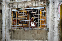"A Cuban woman looks from the barred window in the apartment block in Abel Santamaría, a public housing periphery of Santiago de Cuba, Cuba, 31 July 2008. The Cuban economic transformation (after the revolution in 1959) has changed the housing status in Cuba from a consumer commodity into a social right. In 1970s, to overcome the serious housing shortage, the Cuban state took over the Soviet Union concept of social housing. Using prefabricated panel factories, donated to Cuba by Soviets, huge public housing complexes have risen in the outskirts of Cuban towns. Although these mass housing settlements provided habitation to many families, they often lack infrastructure, culture, shops, services and well-maintained public spaces. Many local residents have no feeling of belonging and inspite of living on a tropical island, they claim to be ""living in Siberia""."