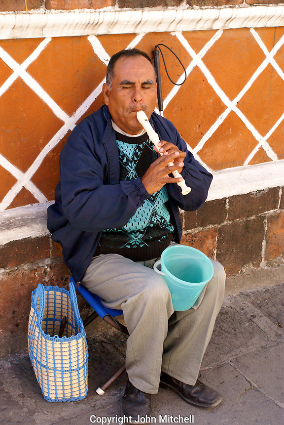 Blind man playing a recorder in the city of Puebla, Mexico. The historical center of Puebla is a UNESCO World Heritage Site..