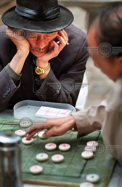 Elderly men playing a board game in a park.