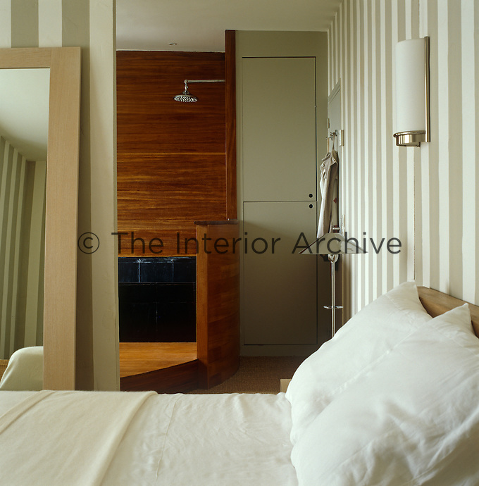 An ensuite bathroom is situated behind a partition in this bedroom