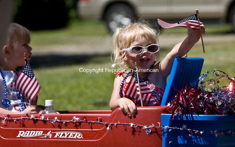 THOMASTON, CT - 04 JULY 2010 -070410JT01-<br /> Megan Campbell, 3, waves an American flag as she rides in a wagon with her cousin, Jackie Phillips, also 3, during the 45th annual Children's Parade, organized by Mary Reynolds, on Sunday in Thomaston.<br /> Josalee Thrift Republican-American