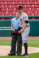 Quad Cities River Bandits manager Mickey Storey (17) talks with home plate umpire Jennifer Pawol during a Midwest League game against the Kane County Cougars on July 1, 2018 at Northwestern Medicine Field in Geneva, Illinois. Quad Cities defeated Kane County 3-2. (Brad Krause/Four Seam Images)