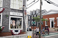 Alex Almonfrey, 25, cleans windows on the Jack Wills storefront in Edgartown, Martha's Vineyard, Massachusetts, USA, on Tues., July 25, 2017.  Almonfrey said he worked on temporary visas in previous years but is now staying in the US permanently. He works primarily as a painter, but also does odd jobs like this window cleaning.