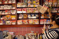 Staff member at Sakura instant ramen restaurant Chie Tanaka works behind the bar. Some of 200 varieties of instant ramen are on the shelves. Owner Sakura Takenaka founded the restaurant 2 years ago and now has 10 franchises over Japan.