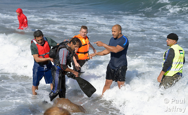 People detain a suspected Turkish migrant smuggler on a beach near Molyvos, on the Greek island of Lesbos on October 31, 2015. He was rescued from the water after volunteers on the island punctured a raft in which he was trying to flee back to Turkey after depositing a load of refugees. He was turned over to the Greek police.